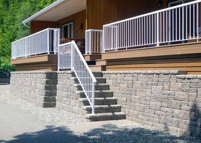 Symmetrical Allan block steps with side railing.